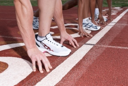 Three athletes on starting blocks on race track, low section